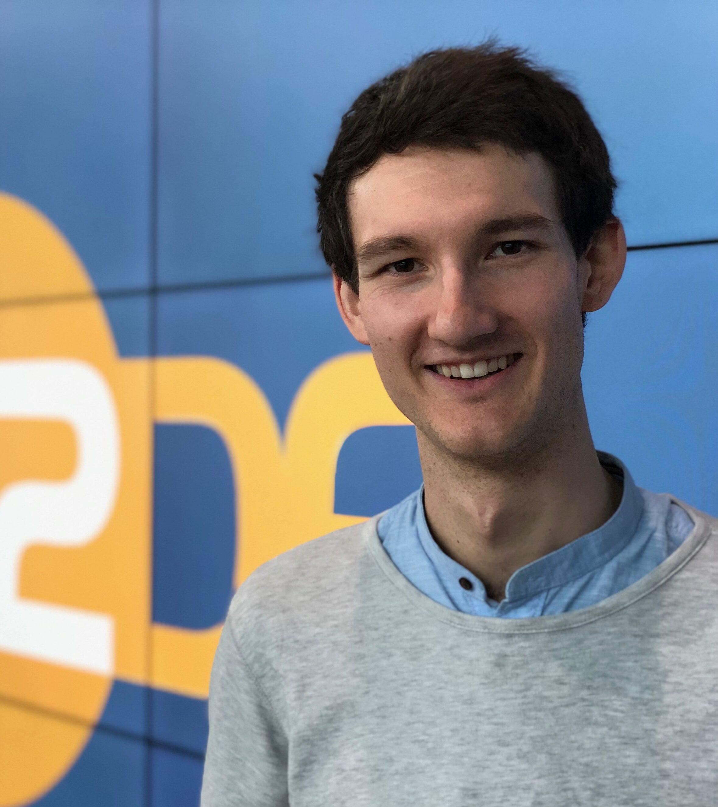 Florian Eib steht vor einer Videowand und lacht in die Kamera. Florian Eib ist studierter Sprach- und Sprechwissenschaftler. Er ist Sprecher für Audiodeskription bei zahlreichen Sportarten, Film und Schauspiel. Bei der gemeinnützigen HörMal Audiodeskription Unternehmergesellschaft ist Florian Eib für Presse- und Öffentlichkeitsarbeit zuständig.
