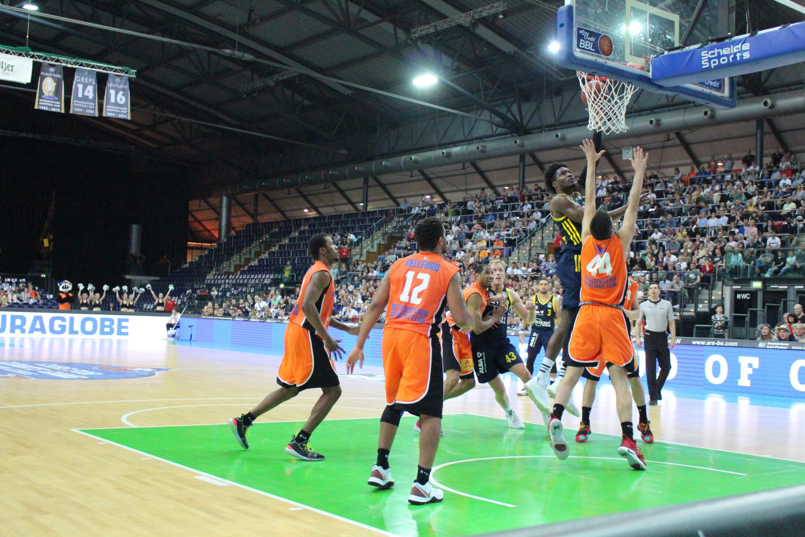 Ein Basketball-Spiel in der Arena Leipzig zwischen dem Mitteldeutschen Basketballclub und Alba Berlin. Ein Berliner Spieler steigt zum Korb hoch und legt den Ball in die Reuse. Alle anderen Spieler springen vergeblich, um ihn vom Netz fernzuhalten.