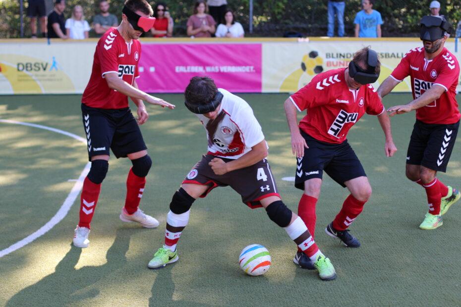 Szene aus der Blindenfußball-Bundesliga: St. Paulis Jonathan Tönsing schirmt den Ball gegen drei Stuttgarter Spieler ab.
