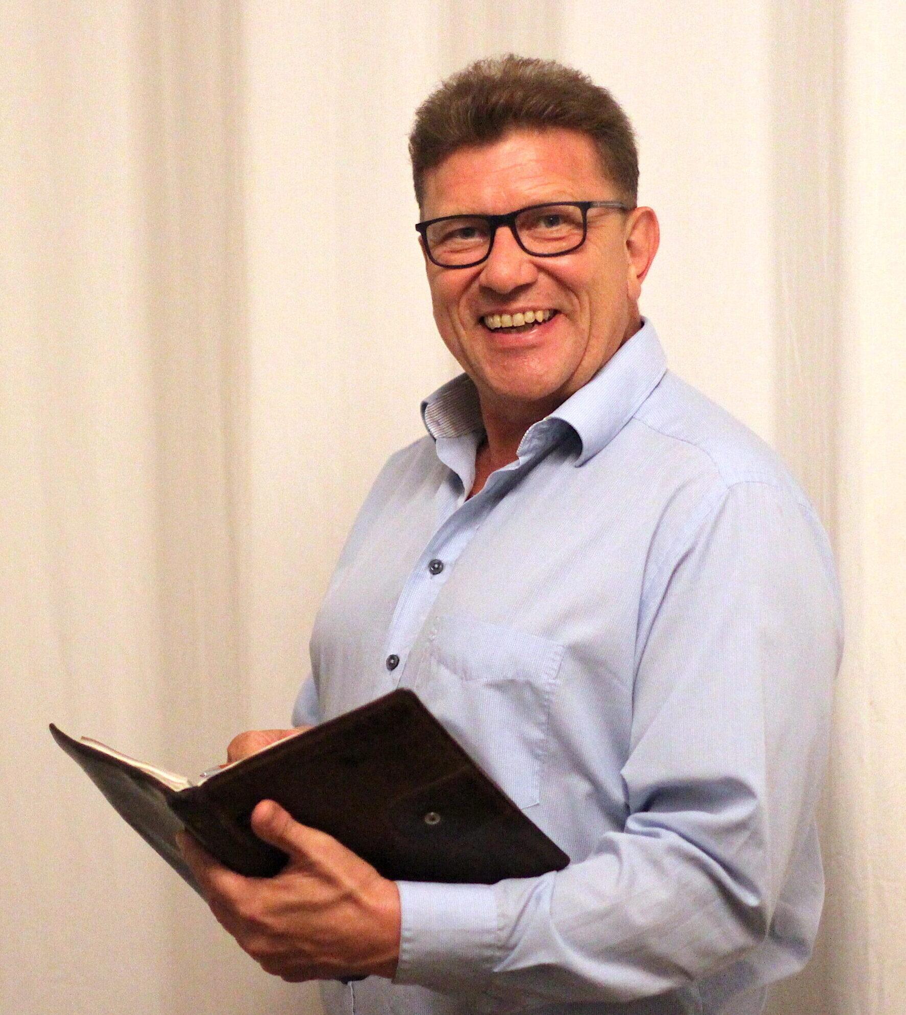 Peter Lomb mit einem Kalender in der Hand. Er ist Geschäftsführender Gesellschafter der gemeinnützigen HörMal Unternehmergesellschaft. Seine Aufgabengebiete sind Veranstaltungen und Förderungen. Er ist außerdem Sprecher für Audiodeskription, Foto: Florian Eib.