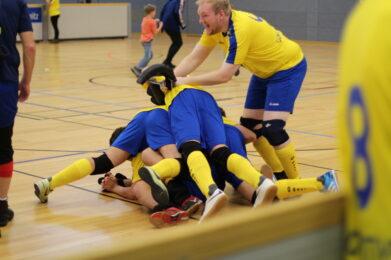 Mehrere Spieler des FC St. Pauli liegen übereinander auf dem Parkettboden. Ein weiterer Spieler springt gerade auf die anderen drauf, Foto: HörMal Audiodeskription.