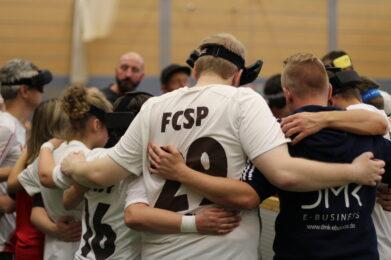 Ein Teamkreis von Spielern des FC St. Pauli. Das Foto zeigt sie mit dem Rücken, sie stehen mit hinter dem Rücken verschränkten Armen zusammen, Foto: HörMal Audiodeskription.