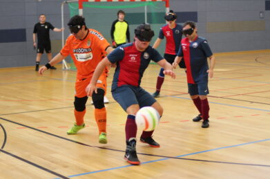 Ein Blindenfußballer kickt den Ball über die Bande ins aus. Er fliegt genau in Richtung des Kamerobjektives, Foto: HörMal Audiodeskription.