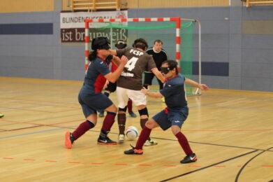 Jonathan Tönsing vom FC St. Pauli dribbelt mit dem Ball in Richtung Tor. Er wird von mehreren Spielern attackiert und setzt sich trotzdem durch, Foto: HörMal Audiodeskription.