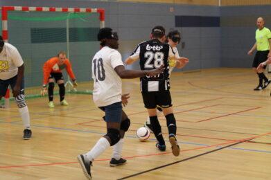 Ein Blindenfußballer im schwarz-weiß-gestreiften Trikot führt den Ball in Richtung Tor. Der Torhüter ist nach unten gebeugt und erwartet einen Schuss, Foto: HörMal Audiodeskription.