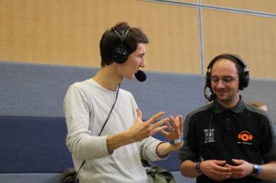 Florian Eib und Felix Amrhein, Reporter für Audiodeskription bei der Arbeit. Sie haben ein Headset auf dem Kopf und beschreiben gestenreich eine Spielszene, Foto: HörMal Audiodeskription.