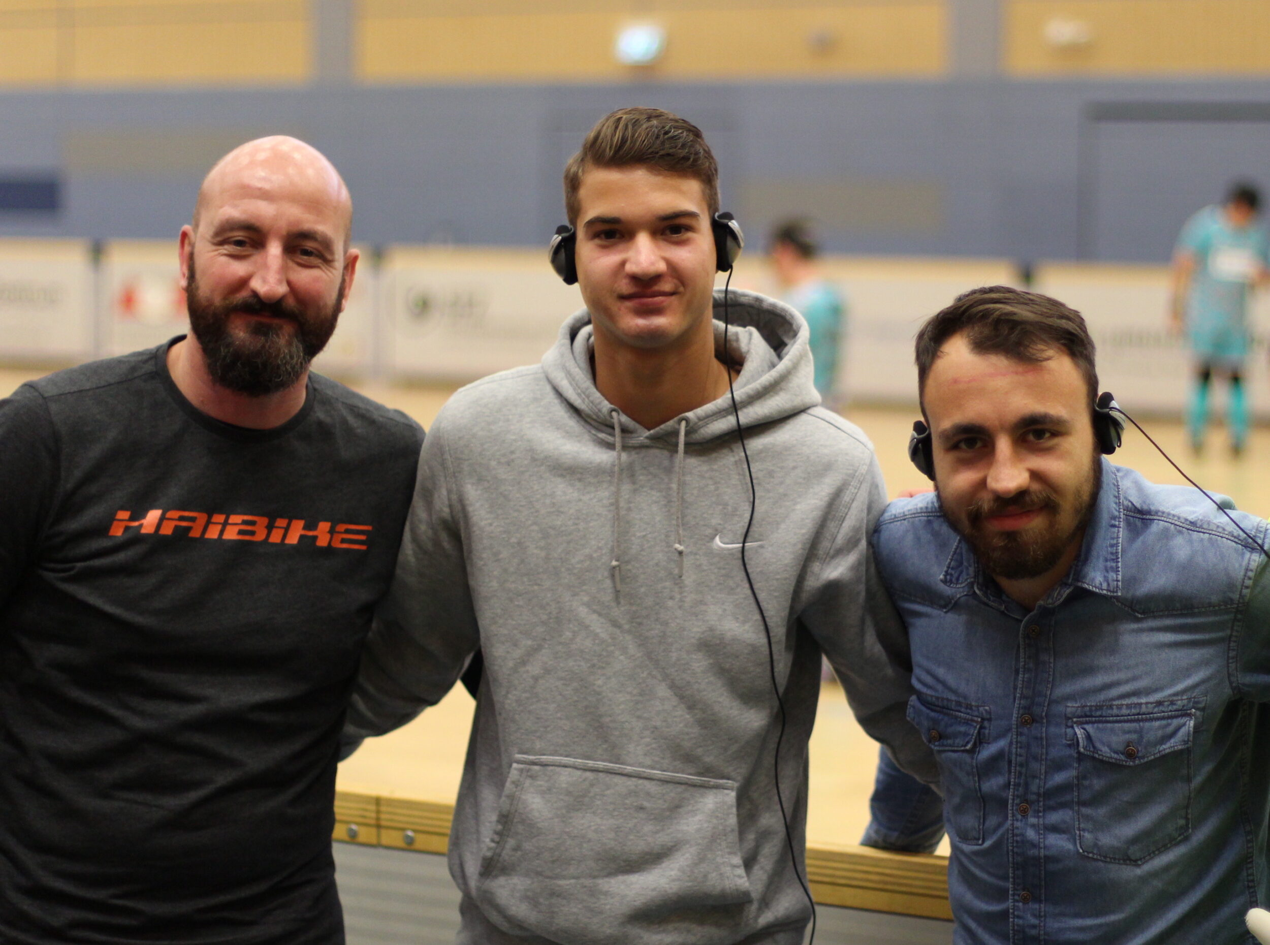 Michael Falb, Blindenfußballtrainer aus Chemnitz sowie die beiden Spieler von Lok Leipzig Robert Berger und Marcel Wagner grinsen in die Kamera. Wagner und Berger haben Kopfhörer auf, mit denen sie die Audiodeskription bei dieser Veranstaltung empfangen, Foto: HörMal Audiodeskription.