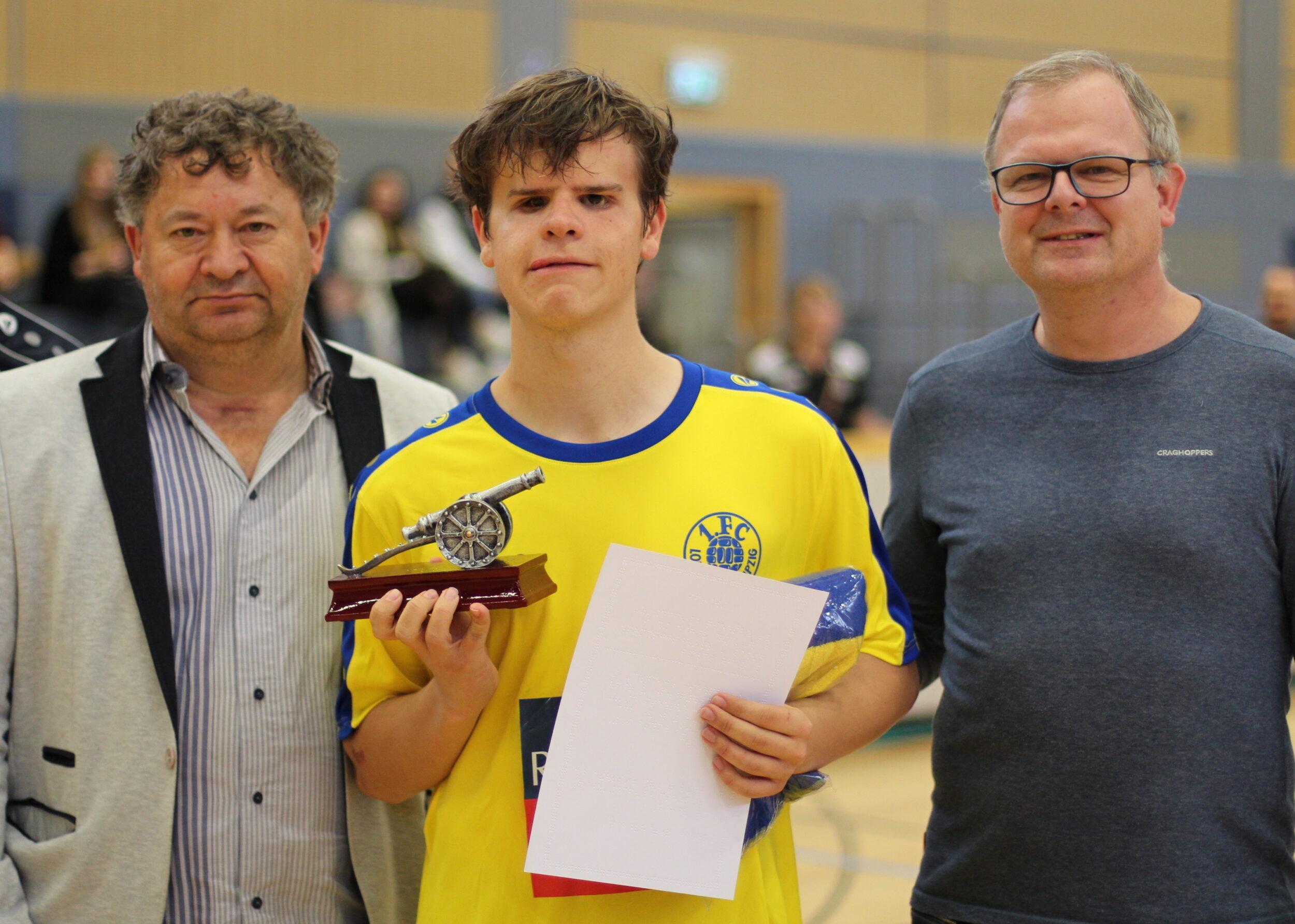 Jonathan Tönsing, eigentlich Spieler des FC St. Pauli, hier im Bild in Trikot des 1. FC Lok Leipzig. Er hat eine Torjägerkanone und eine Urkunde in Braille-Schrift in der Hand, Foto: HörMal Audiodeskription.