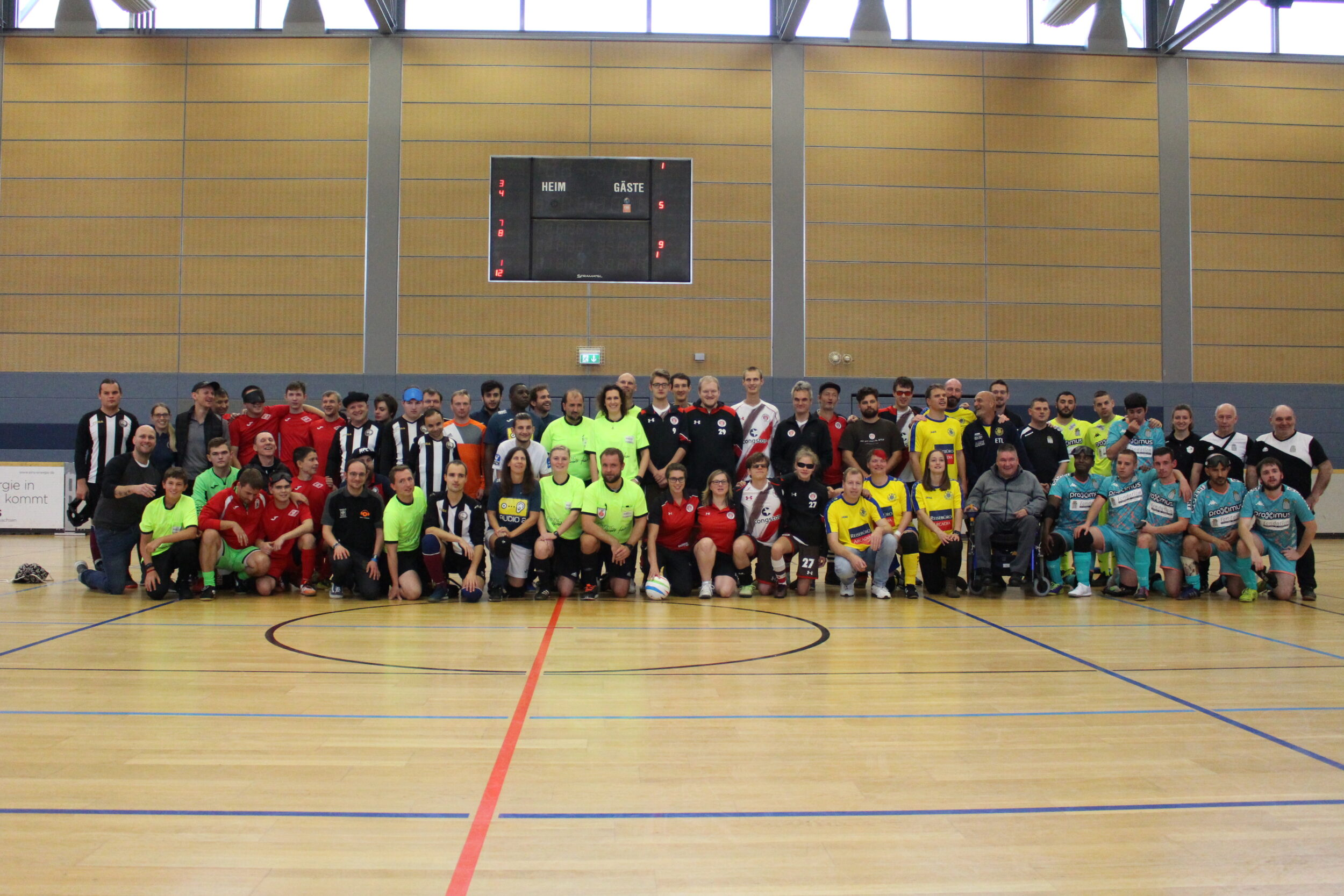 Knapp 70 Personen auf einem Gruppenfoto in einer Sporthalle. Einige haben Trikots in unterschiedlichen Farben an, Foto: HörMal Audiodeskription.