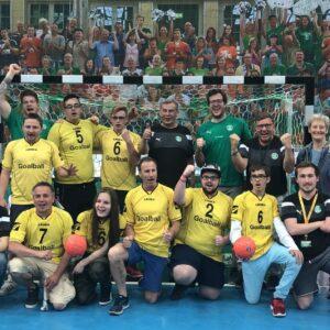 Ein Gruppenfoto mit sehbehinderten und blinden Handballfans, Spielern und einigen Spielern des SC DHfK Handball.