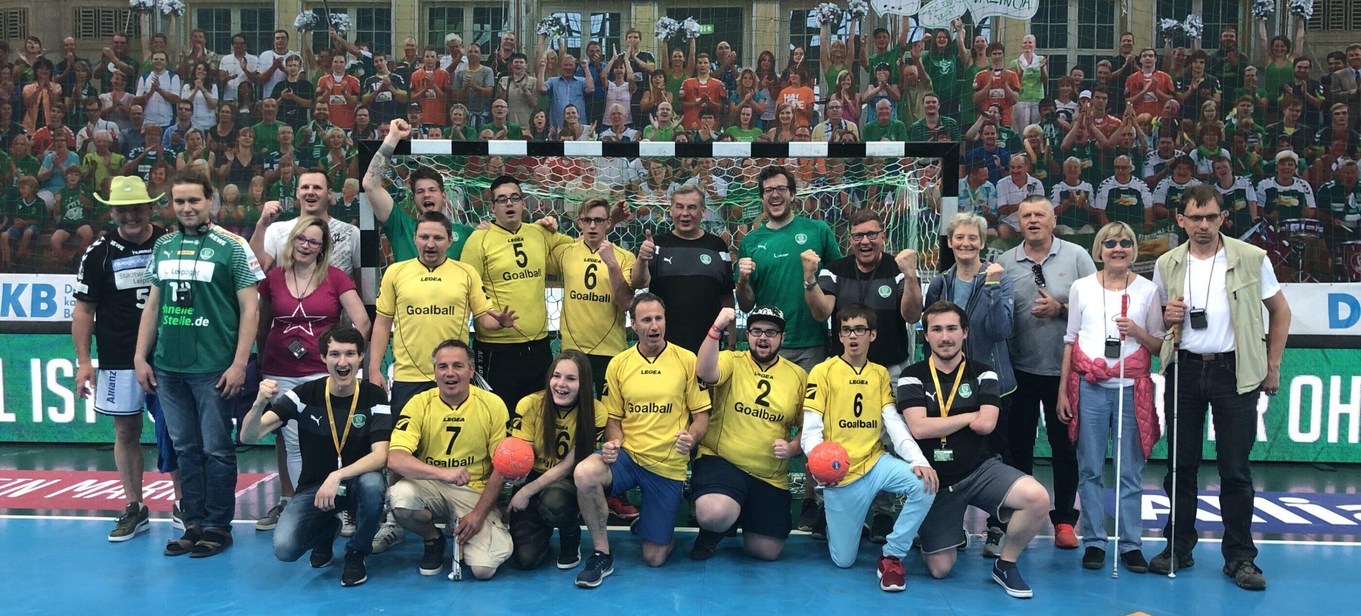 Ein Gruppenfoto mit sehbehinderten und blinden Handballfans, Spielern und einigen Spielern des SC DHfK Handball. Die sehbehinderten und blinden Fans waren bei einer Audiodeskription in der Handball-Bundesliga zu Gast.