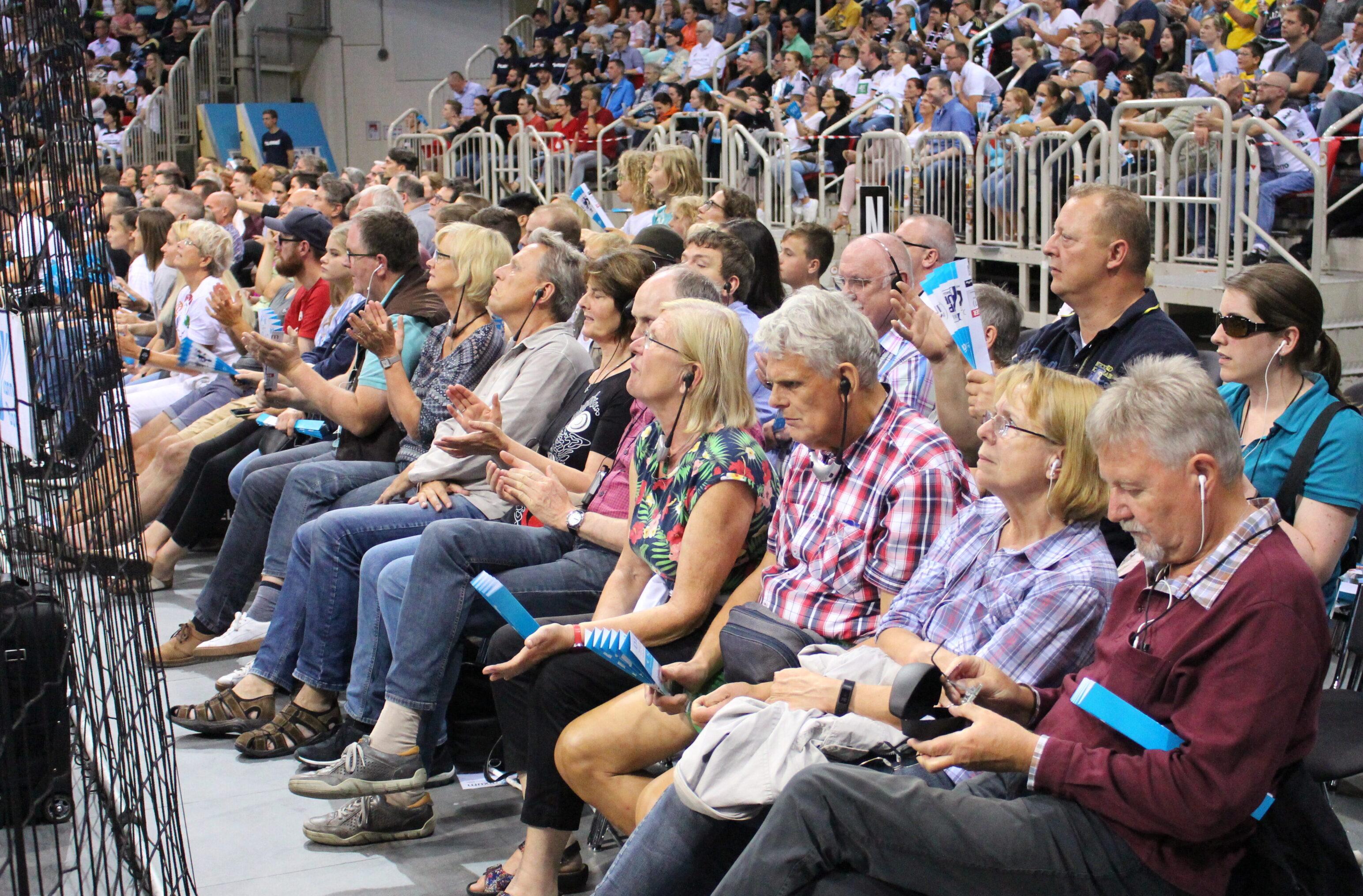 Etwa zwanzig sehbehinderte und blinde Gäste sitzen in zwei Stuhlreihen am Rand eines Handballspielfeldes. Sie haben Kopfhörer auf und empfangen eine Audiodeskription, um dem Handballspiel beim Pixum-Supercup in Düsseldorf folgen zu können.