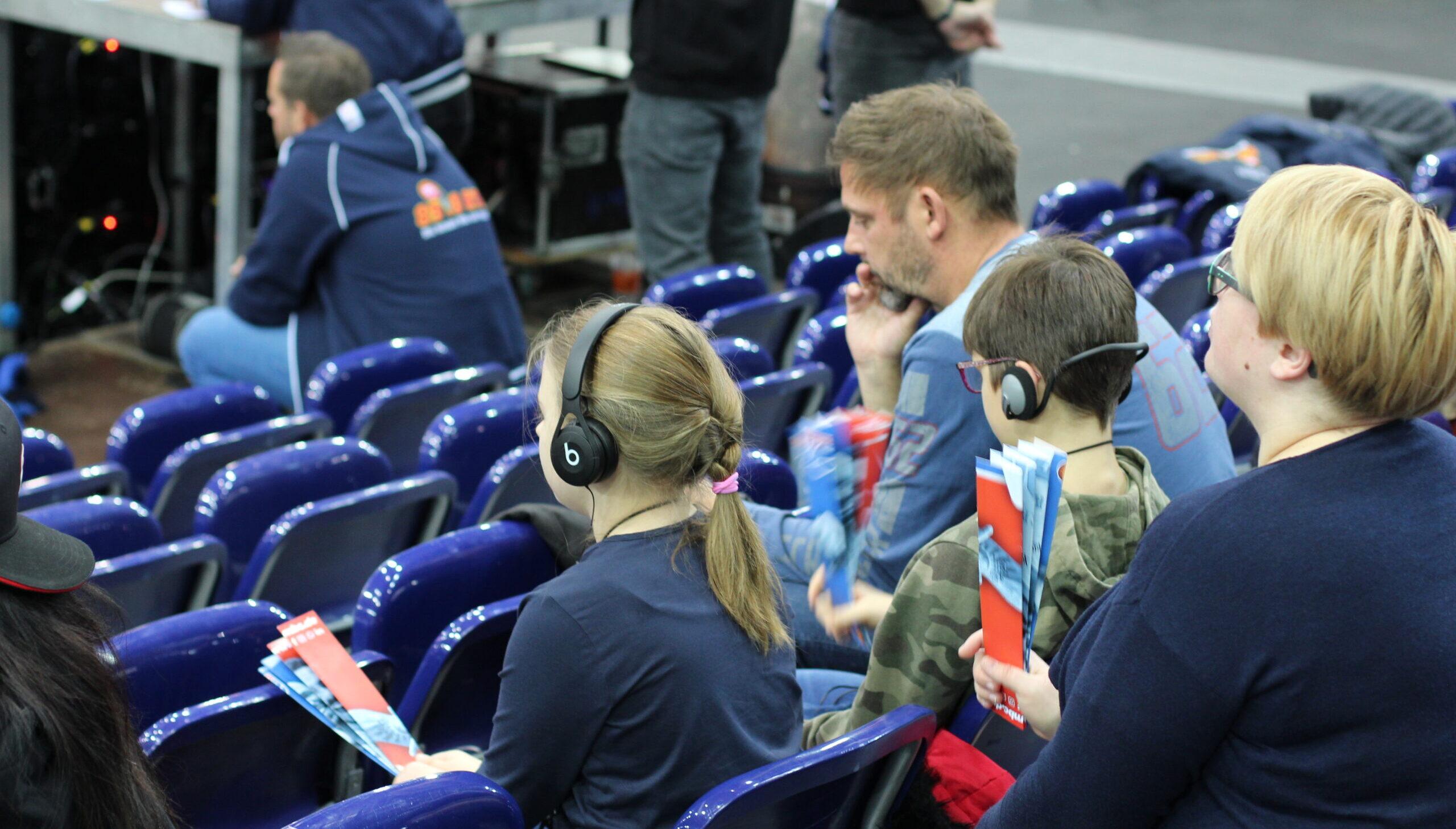 Sehbehinderte und blinde Gäste bei einem Basketballspiel. Über Kopfhörer verfolgen sie die Live-Audiodeskription, die von den HörMal Audiodeskription Reportern Florian Eib und Jari Schaller bereitgestellt wurde.
