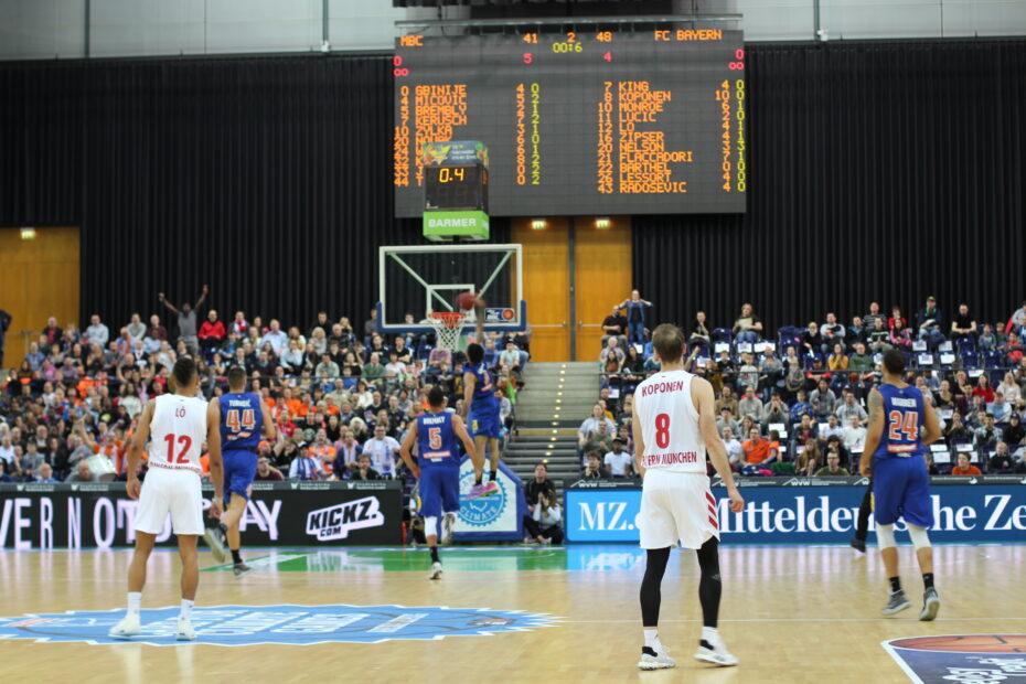 Basketballspieler in blauen und weißen Trikots stehen auf einem Spielfeld und sehen einem Spieler zu, der im Hintergrund mit einem hohen Sprung den Ball in den Korb drückt, Foto: Anneke Elsner.