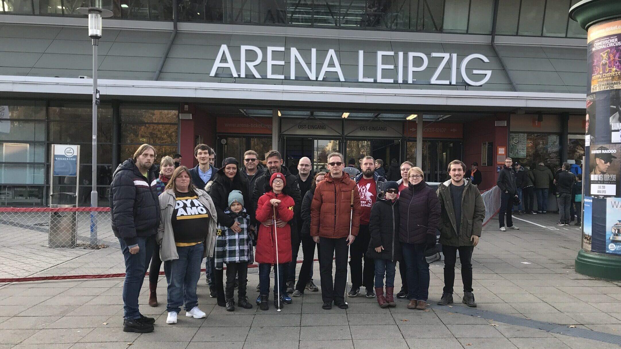 Ein Gruppenfoto vor der Arena Leipzig. Eine Gruppe sehbehinderter und blinder Basketballfans gemeinsam mit Begleitpersonen und den Sprechern für Audiodeskription Florian Eib und Jari Schaller, Foto: Anneke Elsner.