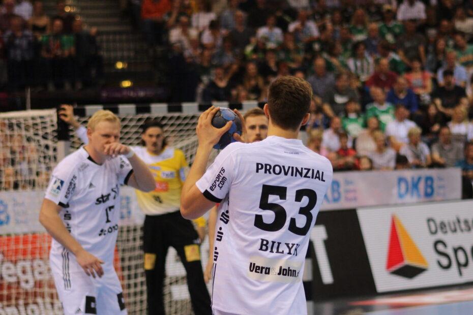 Ein Handballspieler führt einen Ball, im Hintergrund sind seine Mitspieler zu sehen, im Tor ein Torhüter. Im Hintergrund ist eine steil anlaufende Fankurve zu erkennen. Aufnahme vom REWE Final4 in Hamburg 2019, Foto: Florian Eib.