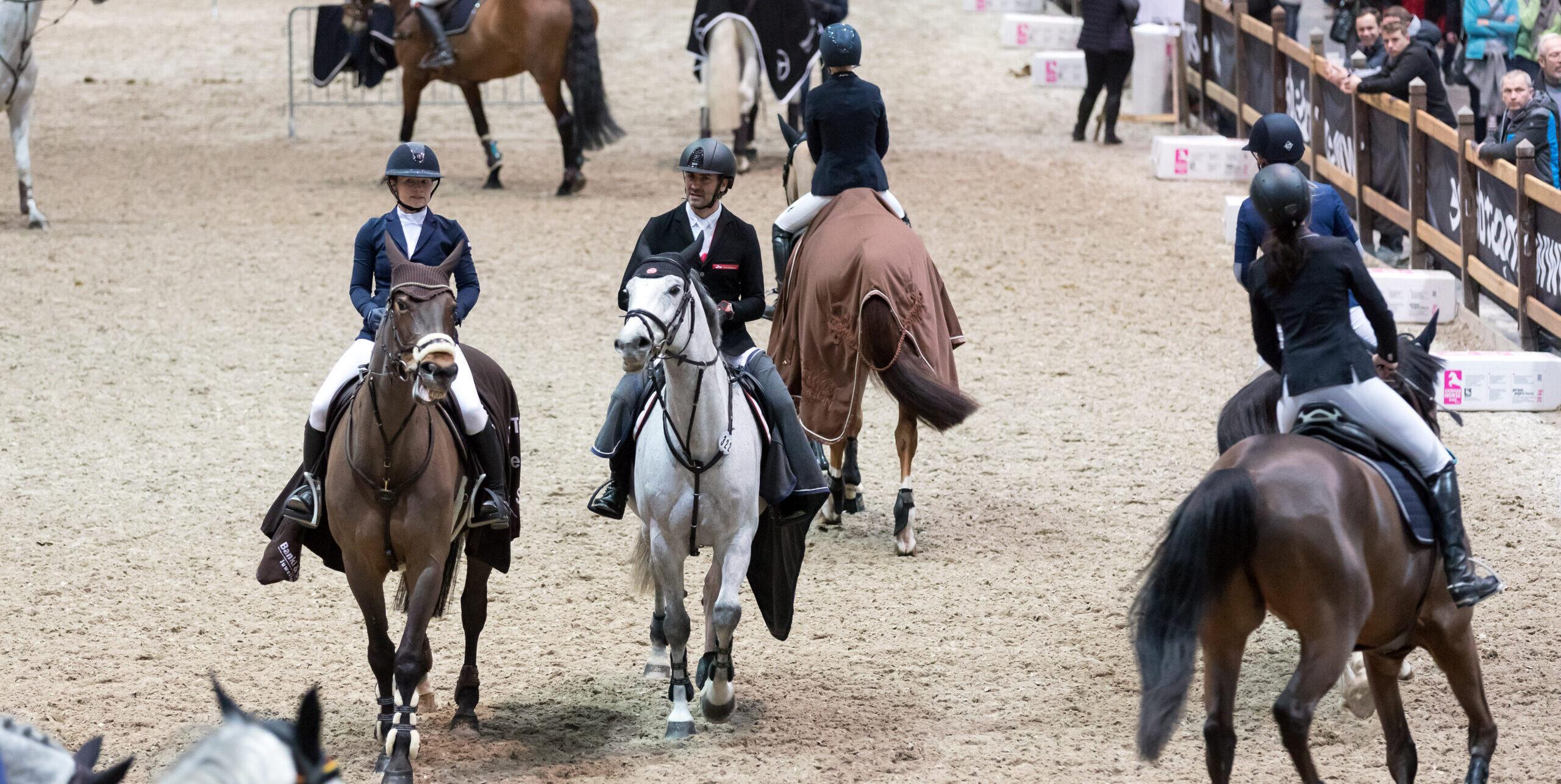 Auf einem Sandplatz reiten Pferdesportler mit ihren Pferden auf und ab. Sie berieten sich für die Sparkassen Sport-Gala vor. An einer Begrenzung des Platzes stehen zahlreiche Besucher, Foto: Tom Schulze.