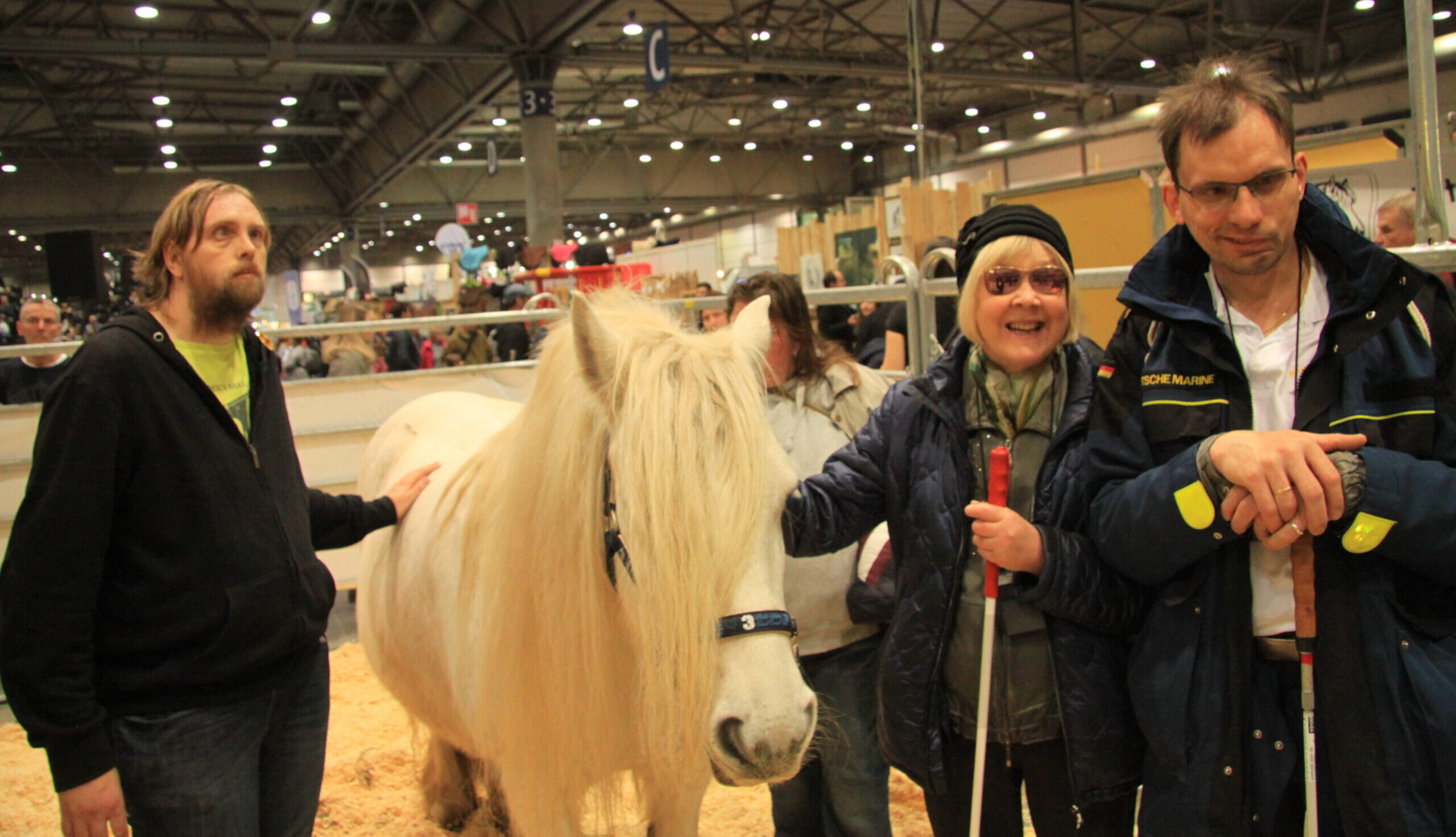 Drei Besucher der PARTNER PFERD mit einer Sehbehinderung stehen neben einem Pony. Das Pony hat eine weiße Farbe und eine lange dichte Mähne, die ihm auf einer Seite vom Kopf hängt. Zwei der Besucher haben eine Hand auf den Rücken des Ponys gelegt, Foto: Kati Lomb.