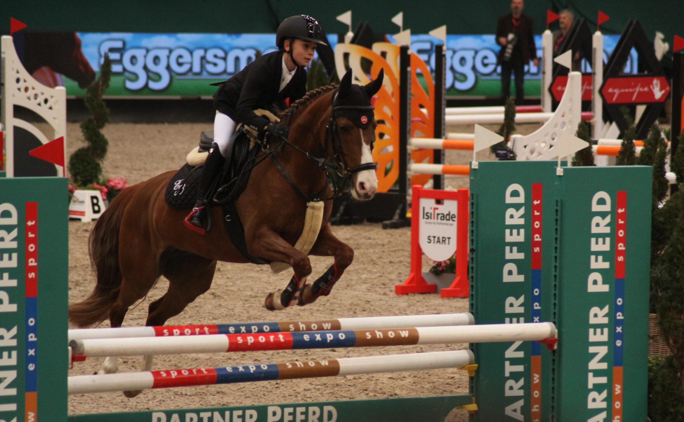 Ein junger Springreiter meistert mit seinem Pferd ein Hindernis. Das Pferd befindet sich mitten im Flug, Foto: Kati Lomb.