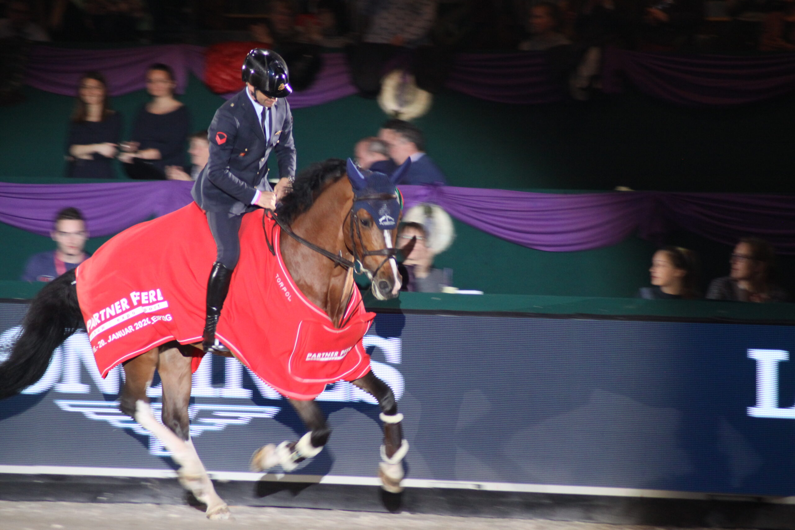 Ein Reiter in einer dunkelblauen Uniform und mit Helm auf dem Kopf sitzt auf einem braunen Pferd. Das Pferd galoppiert und ist in eine rote Decke gehüllt, Foto: Kati Lomb.
