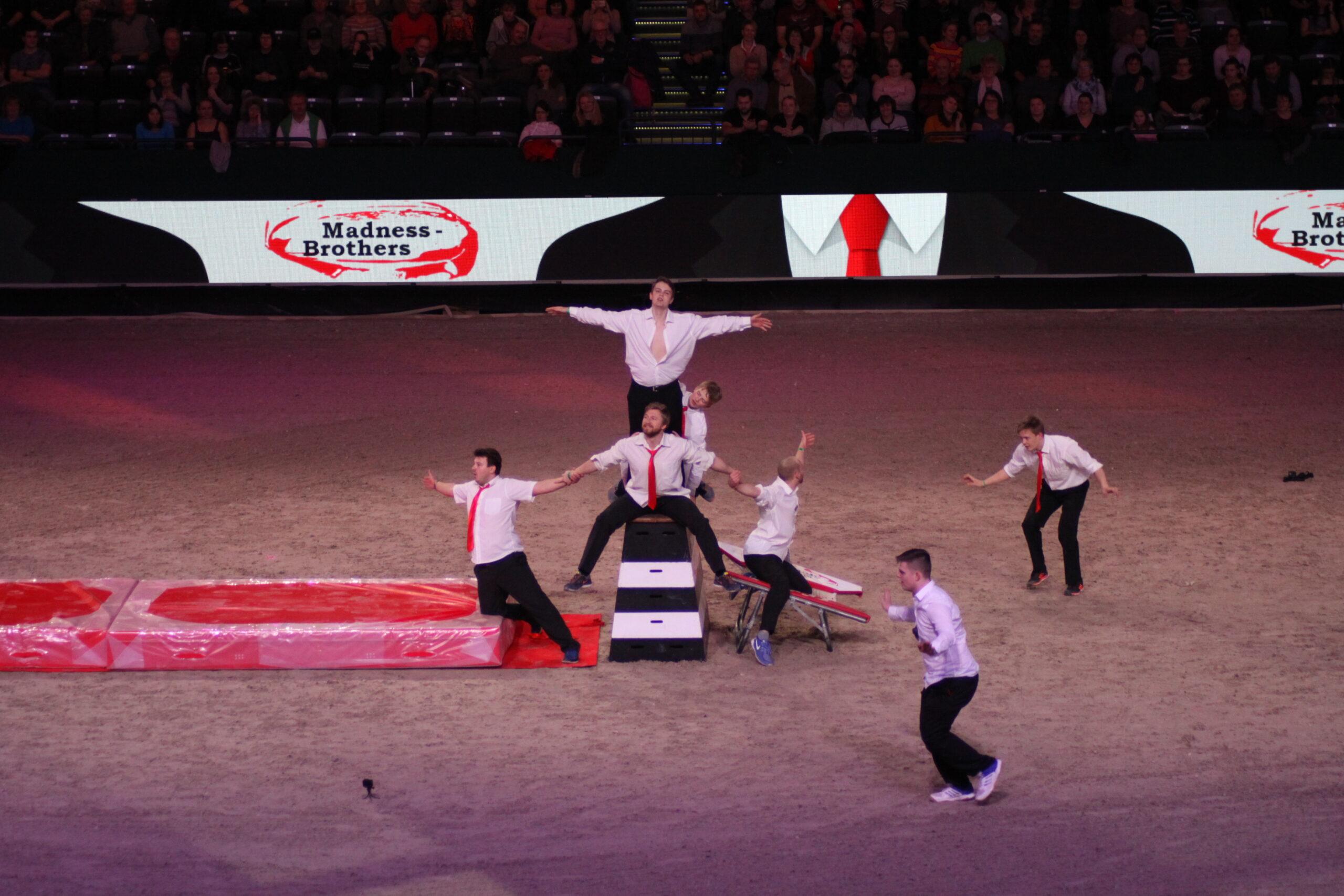 Sieben Männer in weißen Hemden und schwarzen Hosen posieren in einer großen Manege. Sie strecken die Arme aus und und bilden eine Art menschliche Pyramide, Foto: Kati Lomb.