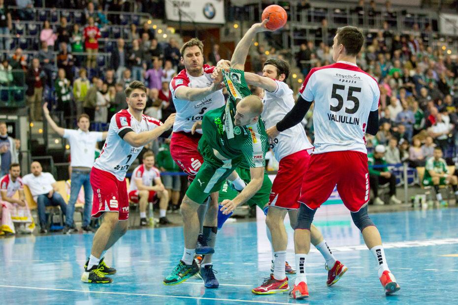 Audiodeskription Handball-Bundesliga: SC DHfK Spieler Maximilian Janke wird von vier Ludwigshafener Spielern Angegriffen. Im Hintergrund sind zahlreiche Zuschauer auf den Rängen.