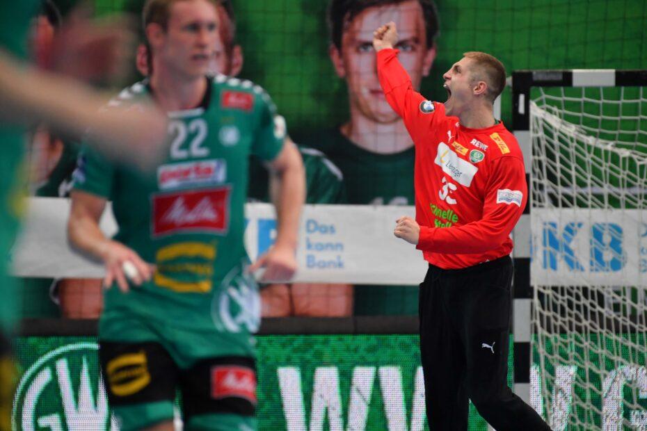 Handball-Bundesliga Audiodeskription: Leipzigs Torhüter Joel Birlehm jubelt mit einer ausgestreckten Faust und in seinem leuchtend roten Torhüter-Trikot, Foto: Rainer Justen.