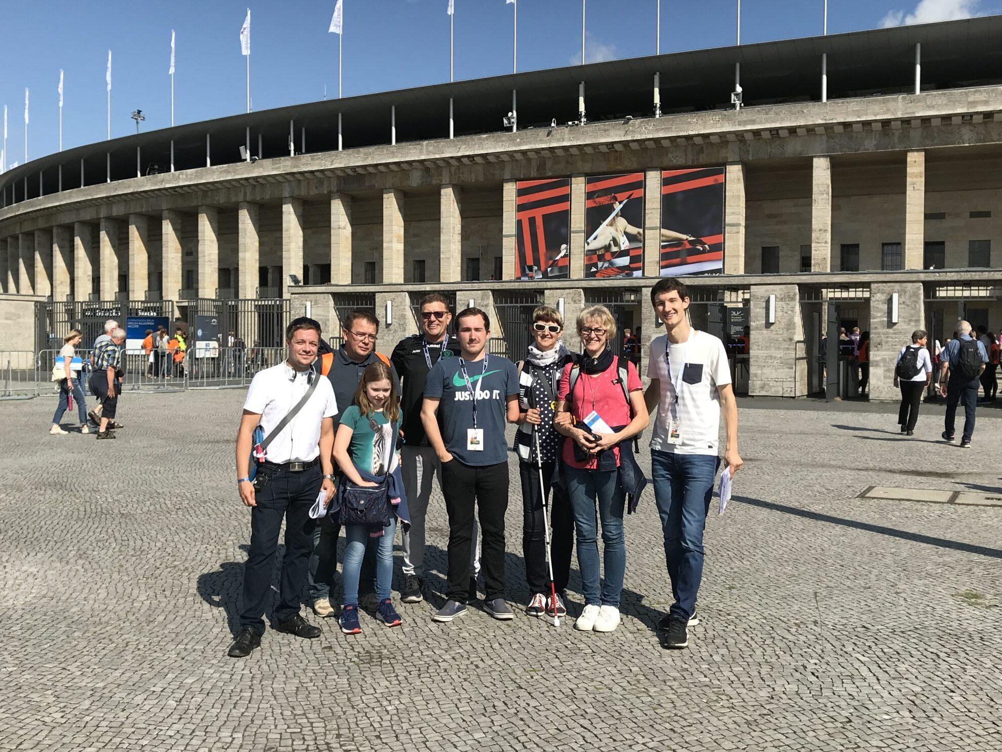 Vor dem Berliner Olympiastadion stehen mehrere Gäste für die Audiodeskription Leichtathletik. Gemeinsam mit den Sprecher der Audiodeskription haben Sie sich zu einem Gruppenfoto aufgestellt. Alle grinsen in die Kamera. Über dem Olympiastadion, das im Hintergrund aufragt, strahlt ein blauer Himmel, Foto: Deutscher Leichtathletik-Verband.