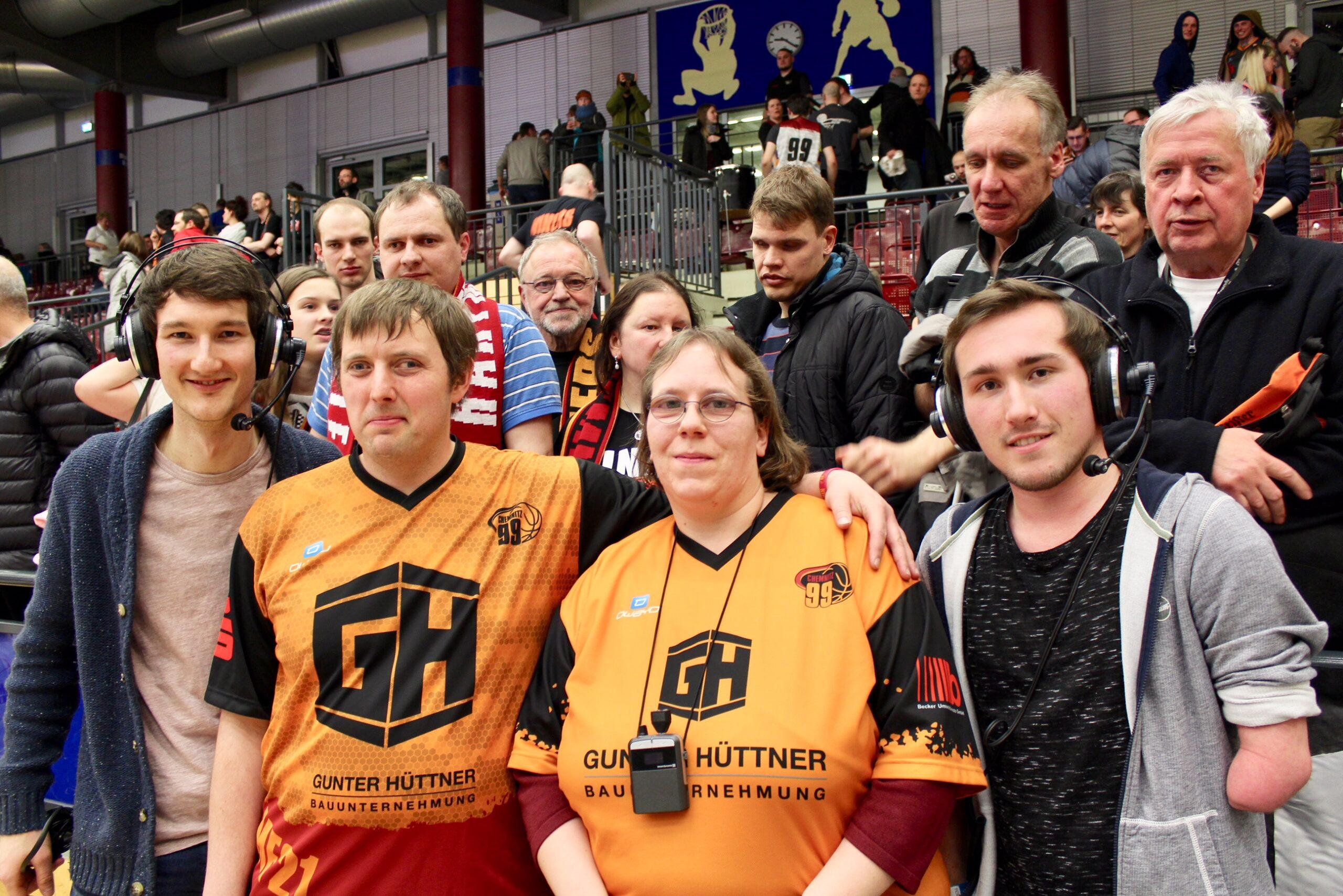 Audiodeskription NINERS Chemnitz: Die Reporter Florian Eib und Jari Schaller, beide mit einem Headset auf dem Kopf, stehen links und rechts neben den Basketballfans Jenifer und Stephan, die in ein orangefarbenes Trikot gekleidet sind. Alle vier grinsen in die Kamera, Foto: Cindy Haase.