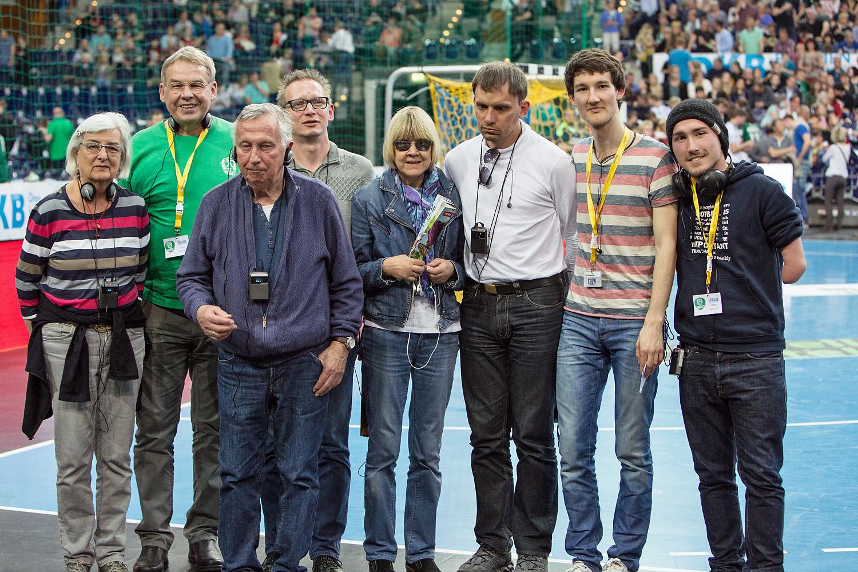 In einer Sporthalle stehen mehrere Handballfans am Spielfeldrand und schauen in die Kamera. Sie haben Hör-Empfänger um den Hals, über die sie eine Spielbeschreibung (Audiodeskription) der Handballspiele empfangen. Im Hintergrund sind volle Tribünen zu sehen, Foto: SC DHfK Leipzig.