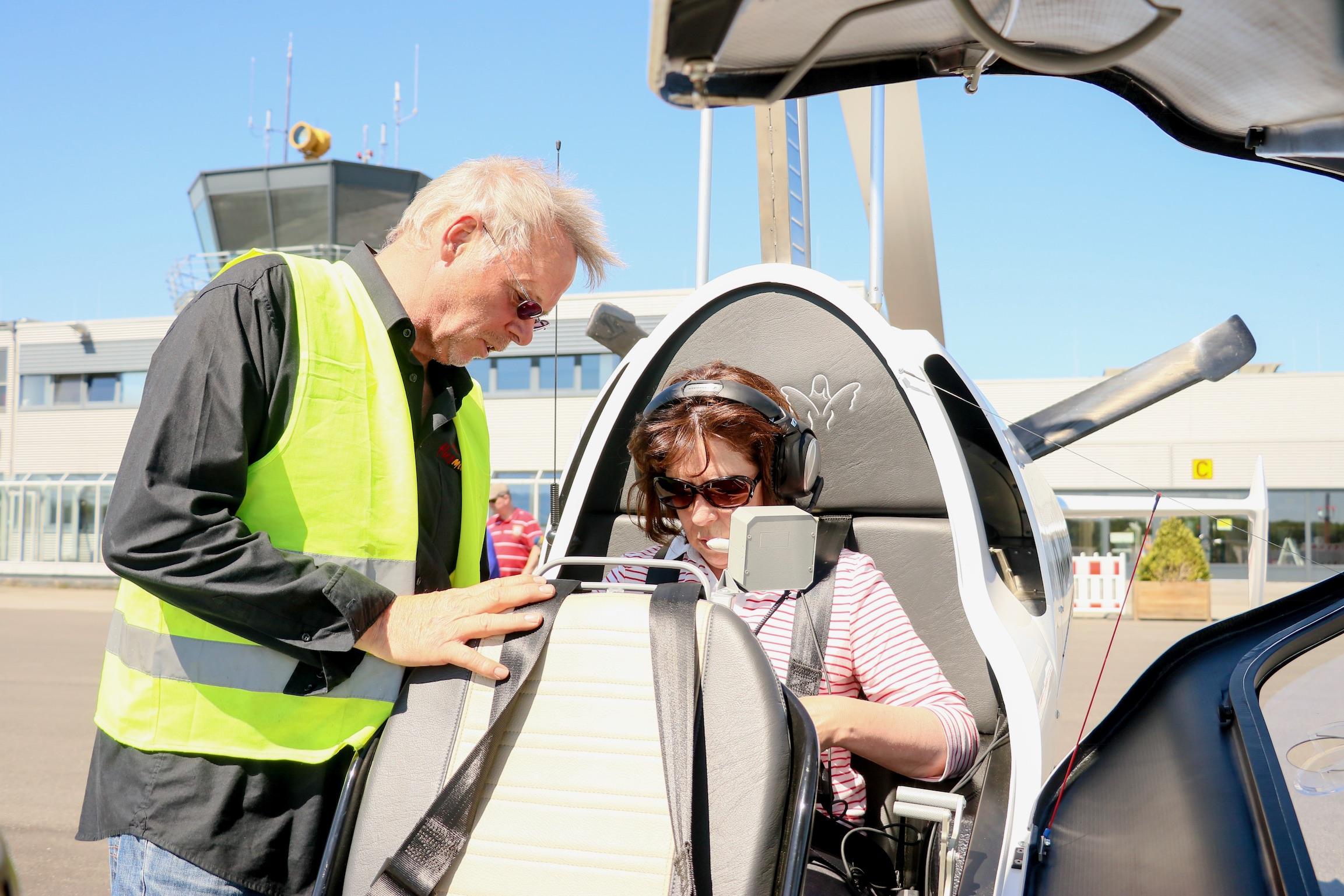 Nahaufnahme eines Tragschraubers auf der Freifläche eines Flughafens. eine Passagierin sitzt im hinteren Teil des Fliegers., Pilot Bernd Koop, der eine gelbe Warnweste trägt, erklärt ihr den Anschnallgurt, Foto: Bastian Kruskop.