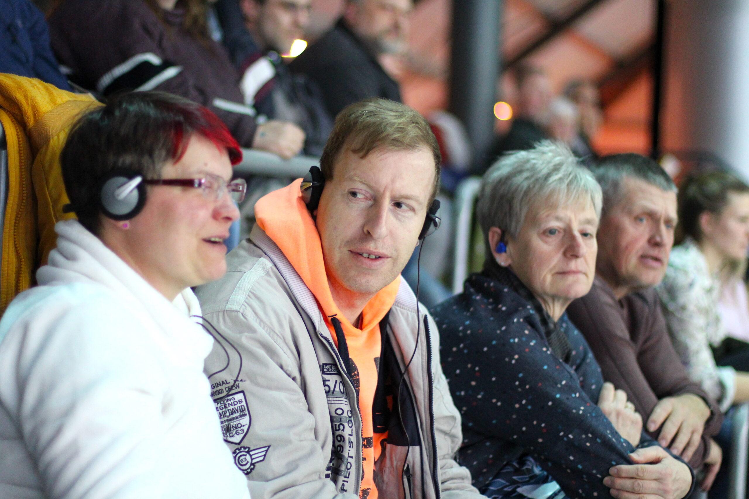 Foto mehrerer Gäste bei den Deutschen Leichtathletik-Hallenmeisterschaften. Einige der Gäste haben Kopfhörer auf, Foto: Tomke Koop.