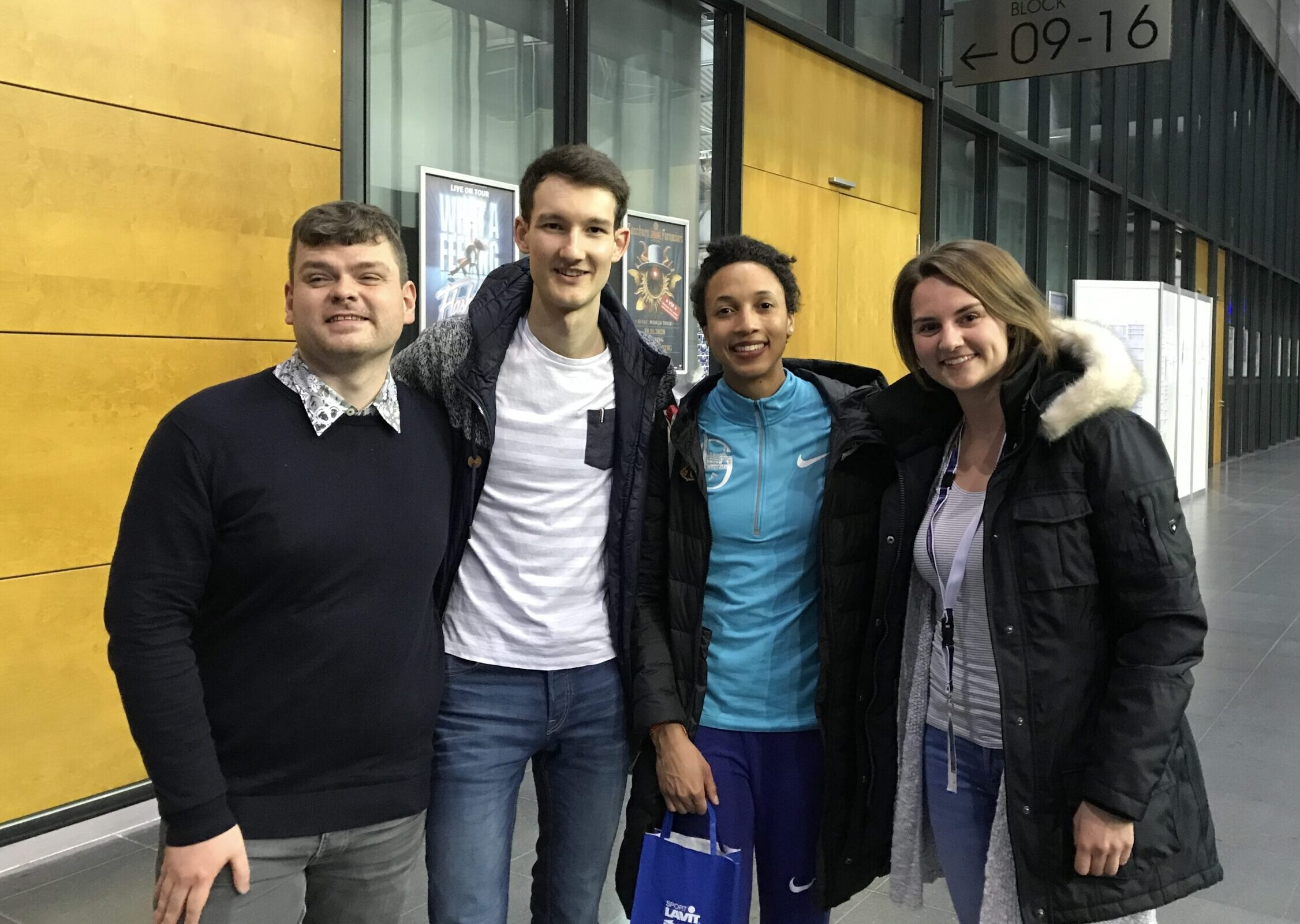 Ein Gruppenfoto mit einem Gast der Audiodeskription, Malaika Mihambo, Florian Eib und Tomke Koop von HörMal Audiodeskription.