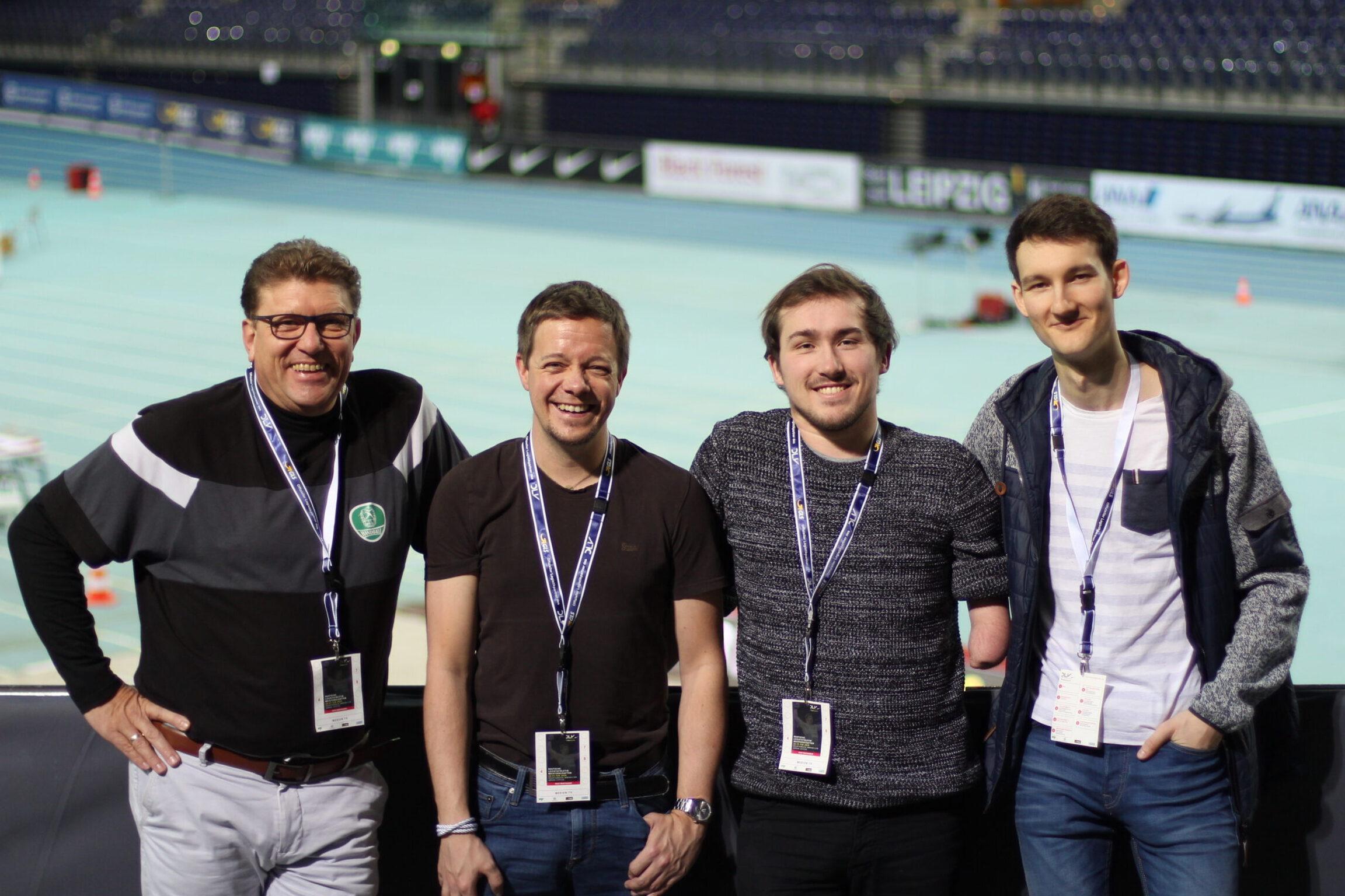 Die Sprecher für Audiodeskription stehen an einer Bande und grinsen in die Kamera. Im Hintergrund ist die Leichtathletik-Arena zu erkennen, Foto: Tomke Koop.