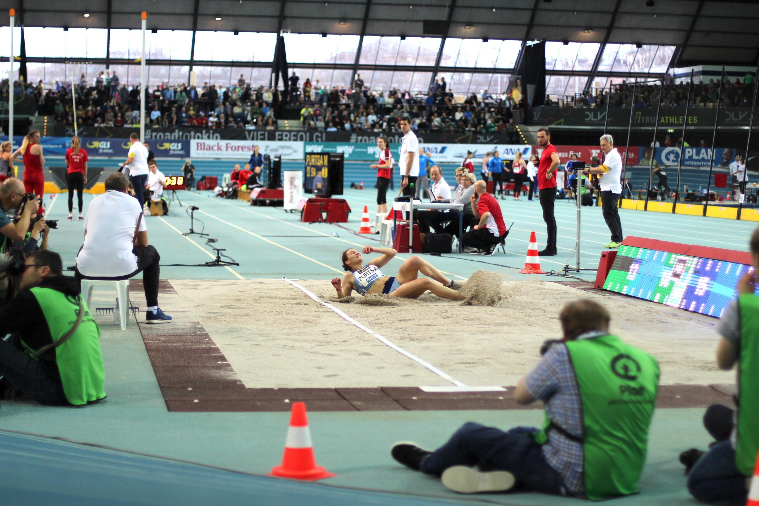 Deutsche Leichtathletik Hallenmeisterschaft 2020: Eine Dreispringerin landet in der Sandgrube und rollt sich seitlich ab. Der Sand spritzt aus der Grube. Die Kampfrichter beobachten die Athletin, Foto: Florian Eib.