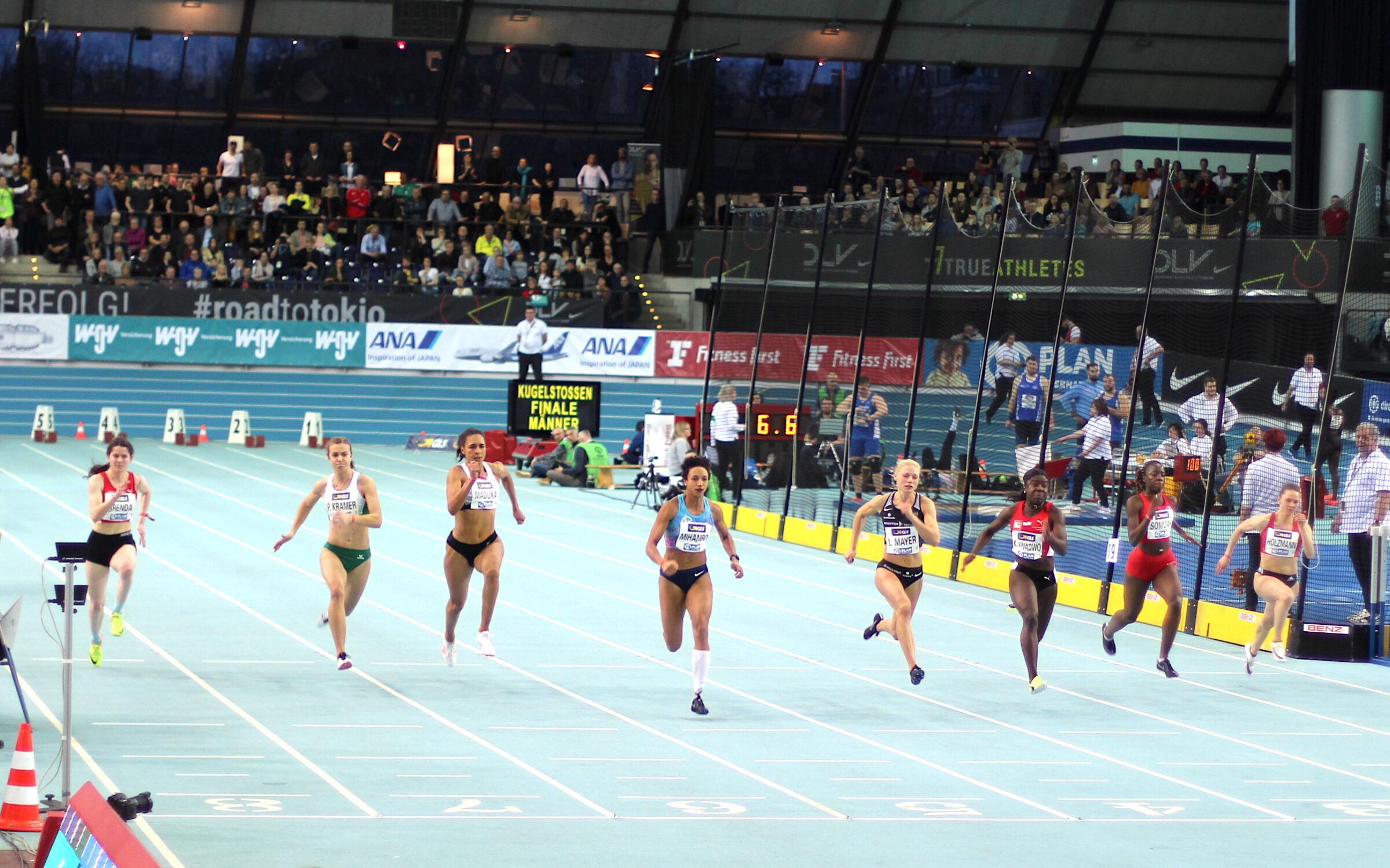 Deutsche Leichtathletik Hallenmeisterschaft 2020: Eine Frontalaufnahme einer Rennbahn in der Leipziger Arena. Acht Sprinterinnen laufen fast parallel nebeneinander her in Richtung Ziellinie, Foto: Tomke Koop.