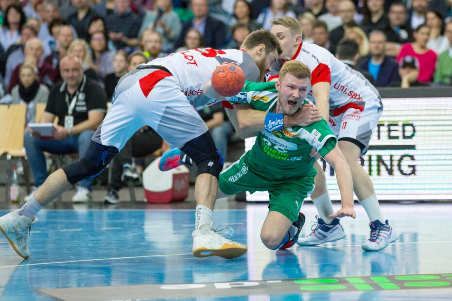 Audiodeskription Handball: Nationalspieler Philipp Weber hat den Ball in der rechten Hand. Er wird von zwei Melsunger Spielern zu Boden gerissen, Foto: Karsten Mann.