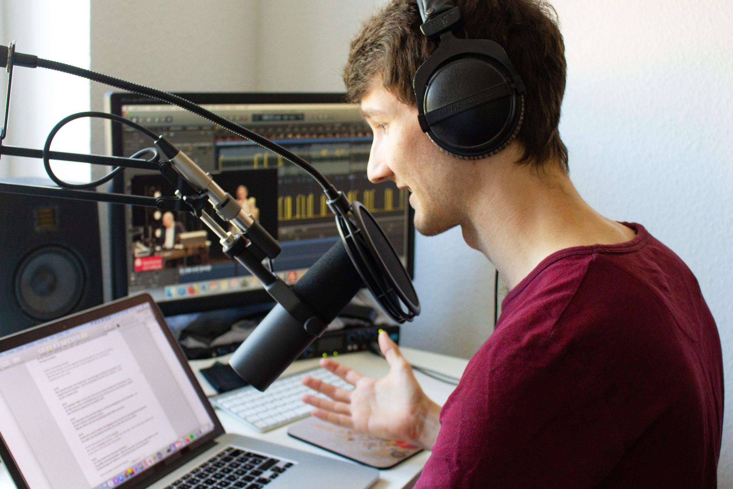 Sprecher Florian Eib sitzt an einem Schreibtisch vor einem Mikrofon. Er blickt auf einen Laptop auf dem ein Text abläuft. Im Hintergrund ein Monitor auf dem ein Aufnahmeprogramm abläuft, Foto: Tomke Koop.