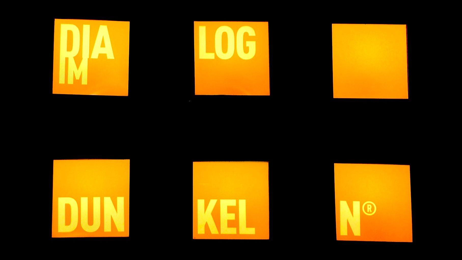 Im Dialoghaus Hamburg: Auf sechs orange beleuchteten Quadraten ist in etwas hellerer abgesetzter Schrift und nach Buchstabengruppen aufgeteilt DIA-LOG-IM-DUN-KEL-N zu lesen, Foto: Florian Eib.