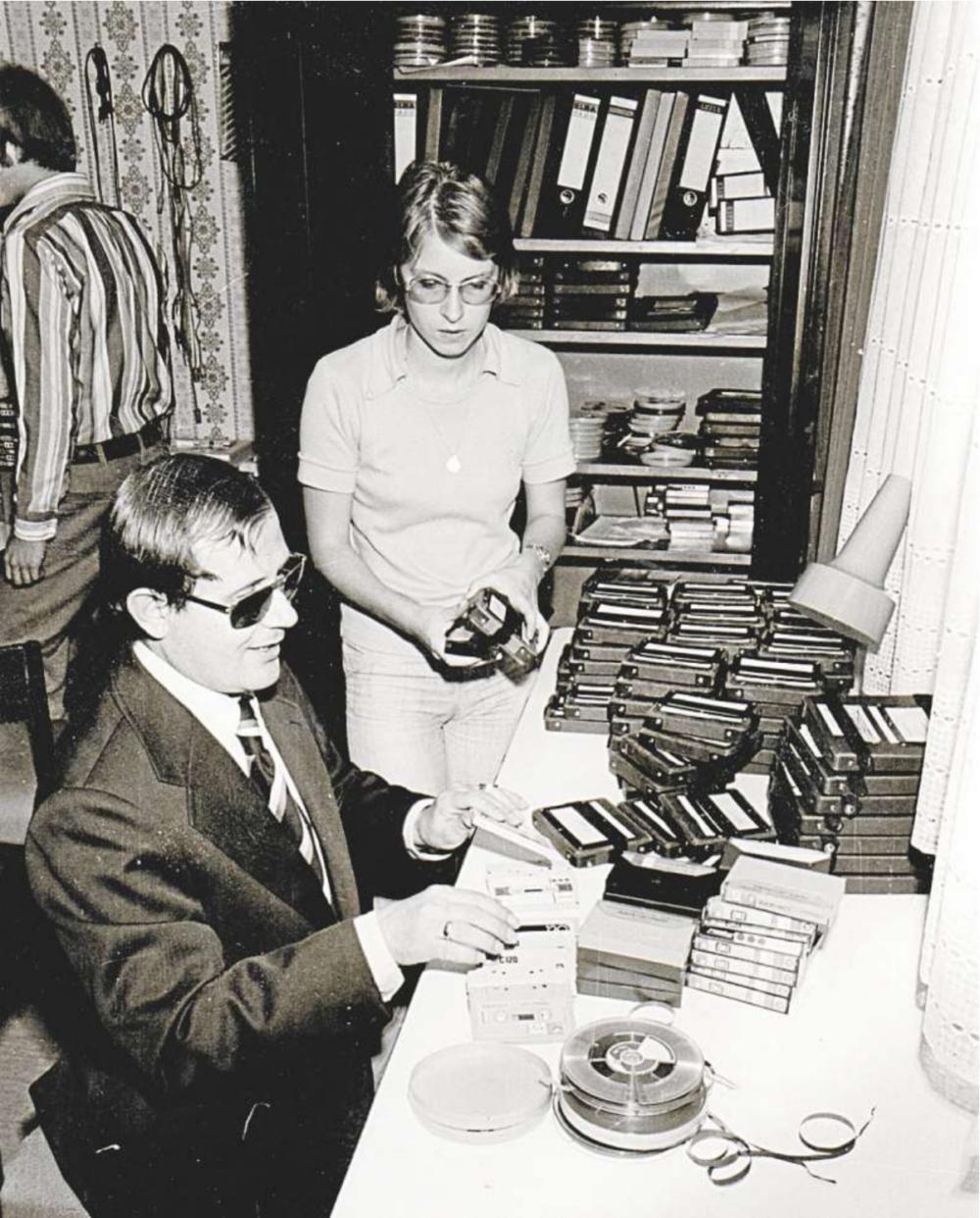Eine Schwarzweißaufnahme zeigt zwei Personen an einem Tisch mit vielen Kassetten und Tonbändern darauf. Eine Person ist Hans-Dieter Sailer, den Wegbereiter der atz Hörmedien. Er trägt Anzug und Schlips und eine dunkle Brille. Sailer tastet an mehreren ausgepackten Kassetten. Neben ihm steht eine jüngere Frau mit Brille. Sie beobachtet ihn und hat ein eingepacktes Spulentonband in der Hand. Im Hintergrund steht ein offener Schrank mit Ordnern und weiteren zahlreichen Tonbandspulen darin, Foto: atz Hörmedien.