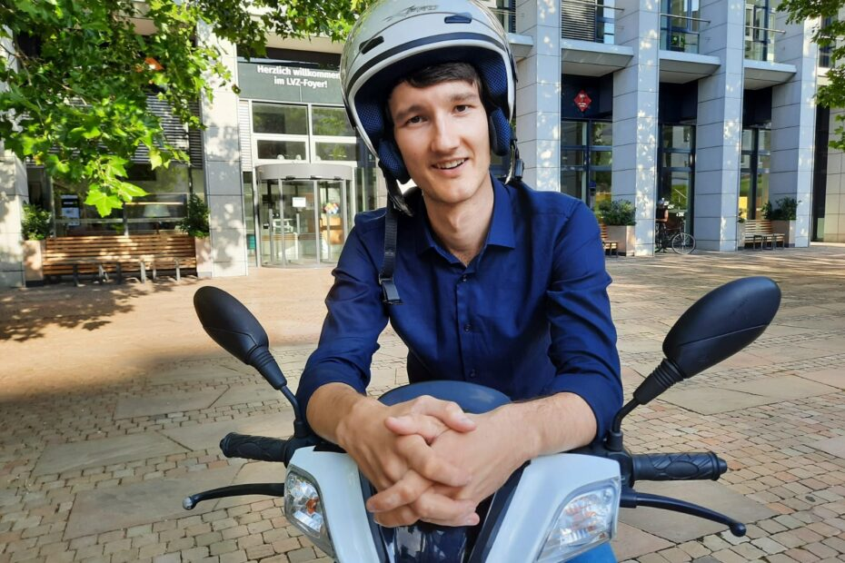 Handball für Blinde: Florian Eib sitzt lässig auf seinem Motorroller und hat einen Helm auf dem Kopf und lächelt in die Kamera. Er trägt ein blaues Hemd und Jeans. Im Hintergrund ragt das Gebäude der Leipziger Volkszeitung auf, Foto: Regina Katzer.