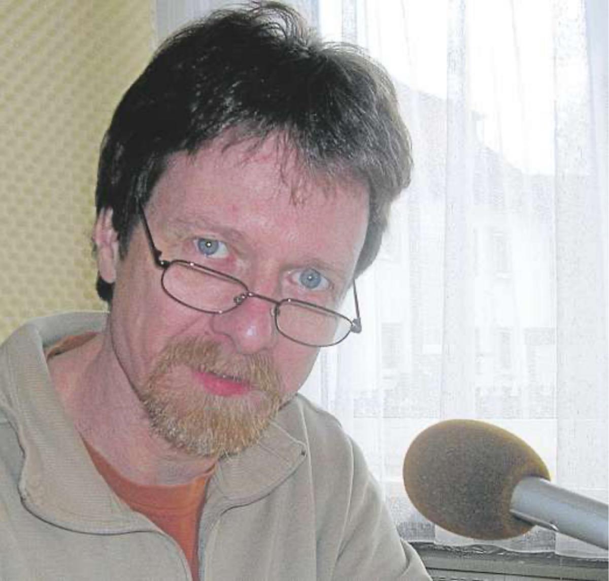 Ein Portraitfoto zeigt Hermann Dremel neben einem Mikrofon. Hermann schaut über den Rand seiner Lesebrille in die Kamera, Foto: atz Hörmedien.