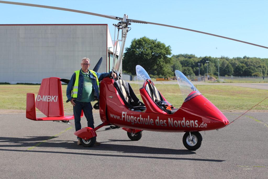 Blindenfliegen: Ein Farbfoto zeigt Bernd Koop auf dem Flughafen Lübeck. Er steht neben seinem roten Tragschrauber. Der Tragschrauber ist ein offenes Fluggerät mit zwei hintereinanderliegenden Sitzen. Ähnlich wie ein Hubschrauber hat der Tragschrauber einen großen Rotor mit zwei langen Rotorblättern. Foto: Florian Eib.