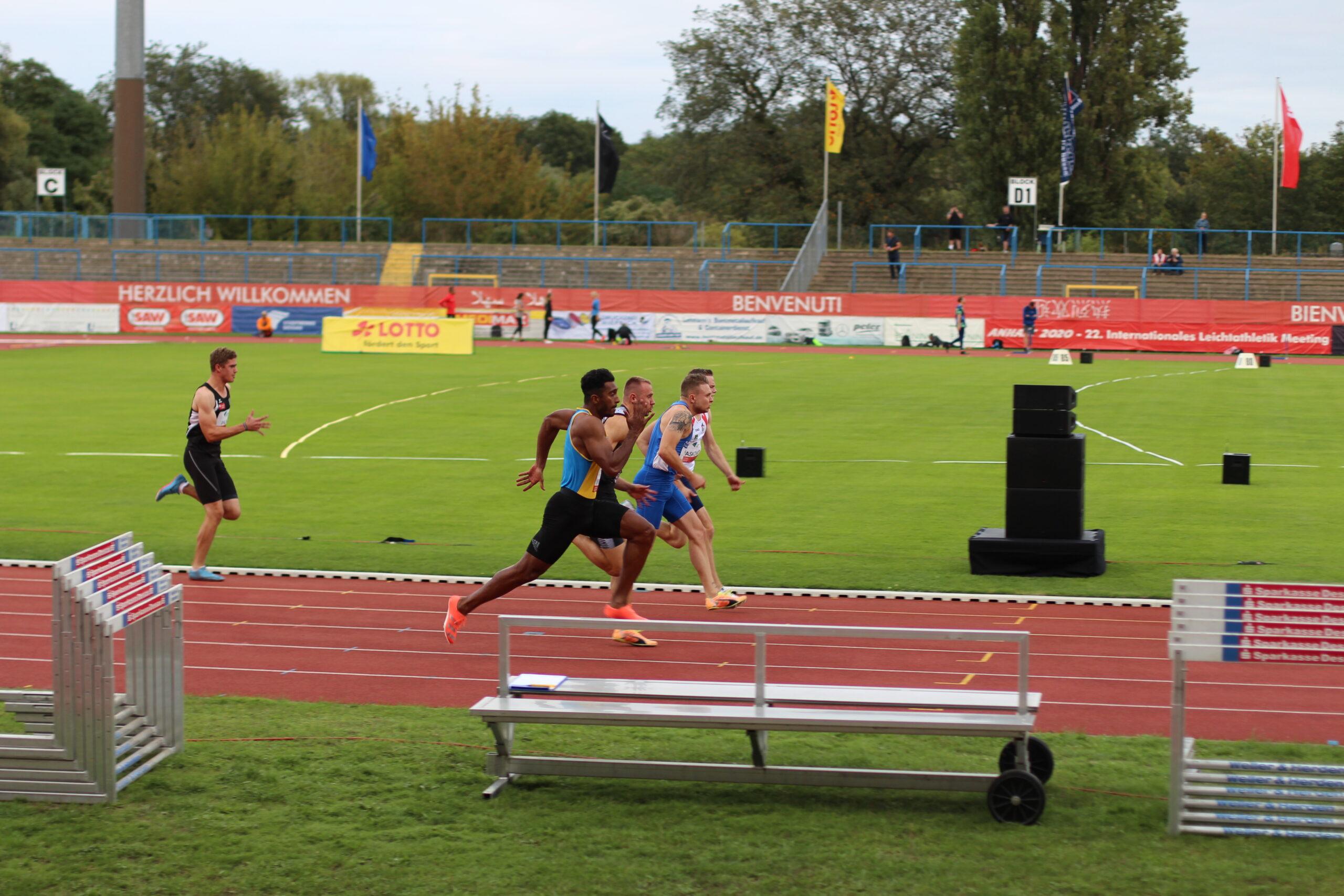 ANHALT 2020 mit Audiodeskription – Seitenblick auf die 100-Meter-Sprintbahn im Paul-Greifzu-Stadion, wo gerade vier Läufer Kopf an Kopf von links nach rechts vorbeilaufen. Ein weiterer Läufer ist bereits zwei Meter hinter ihnen abgeschlagen, Foto: Tomke Koop.