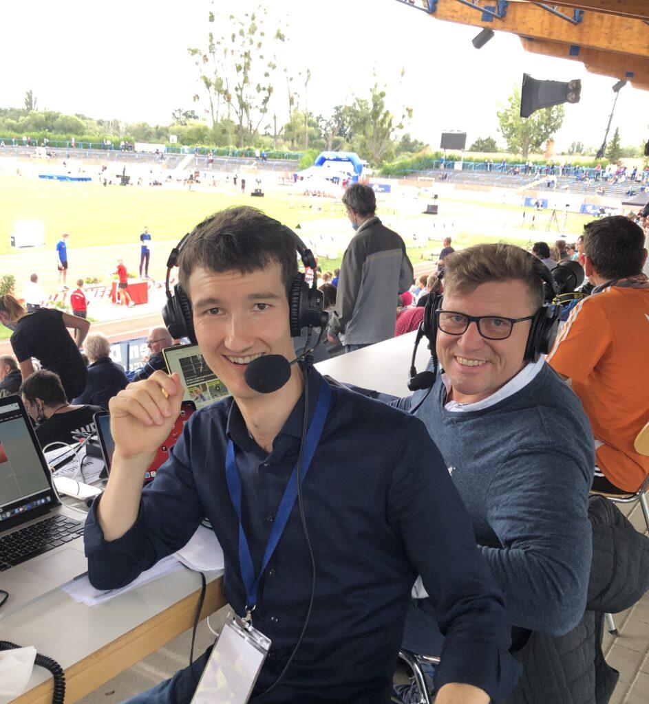 ANHALT 2020 mit Audiodeskription –Peter Lomb und Florian Eib sitzen an einem Reportertisch im Zuschauerbereich des Paul-Greifzu-Stadions. Auf dem Tisch stehen Laptops. Beide haben Headsets auf und lächeln in die Kamera. Sie werden die Geschehnisse für sehbehinderte und blinde Gäste des Events beschreiben, Foto: Tomke Koop.