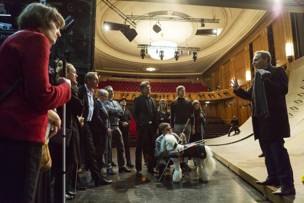 Audiodeskription am Schauspiel Leipzig: Ein Farbfoto von der Bühne des Schauspiels in Leipzig. Auf der Bühne links im Bild stehen mehrere Personen im Halbkreis. Einige davon mit Blindenstock sowie einem Führhund. Die Personen richten ihre Blicke auf einen Mann rechts im Bild, der mit seinen Händen erklärende Gesten macht. Hinter dem Mann sind Holzkonstruktionen aufgebaut. Hinter der Bühne befindet sich der leere Zuschauerraum.