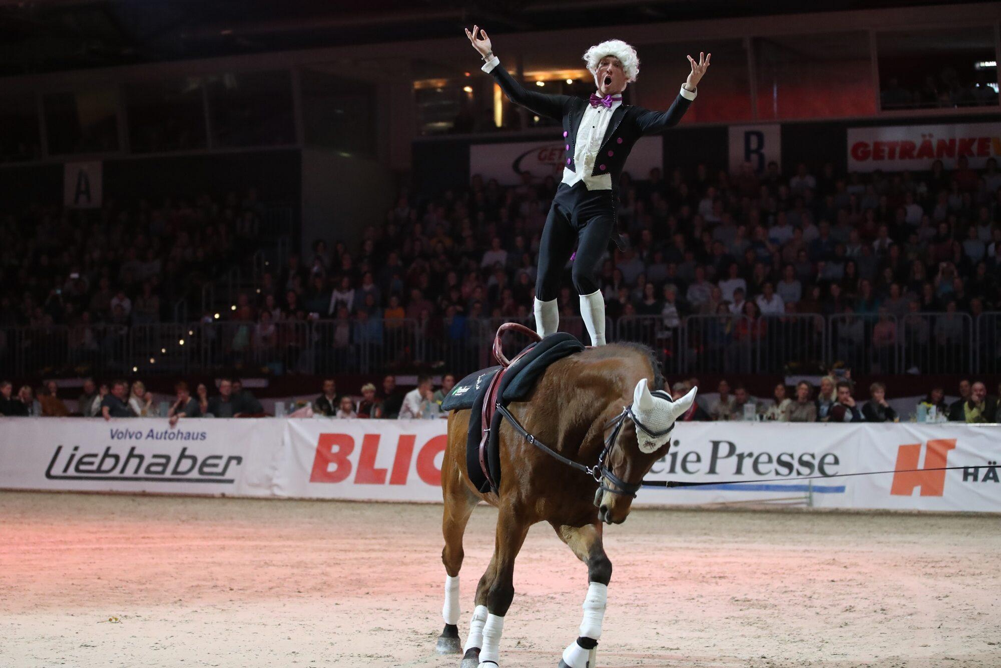 Chemnitzer Pferdenacht mit Audiodeskription: In einer Reitarena steht ein Mann mit Perücke und barockem Anzug auf einem trabenden Pferd. Gestikulierend hat er seine Hände zur Seite gehoben. Im Hintergrund füllen Zuschauer die Sitzplätze, Fotoquelle: www.großer-preis-sachsen.de.