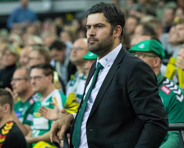 Karsten Günther in Jacket, mit weißem Hemd und grüner Krawatte. Er schaut konzentriert. Im Hintergrund sitzen zahlreiche Fans mit grün-weißen Trikots und Klatschpappen, Foto: Karsten Mann