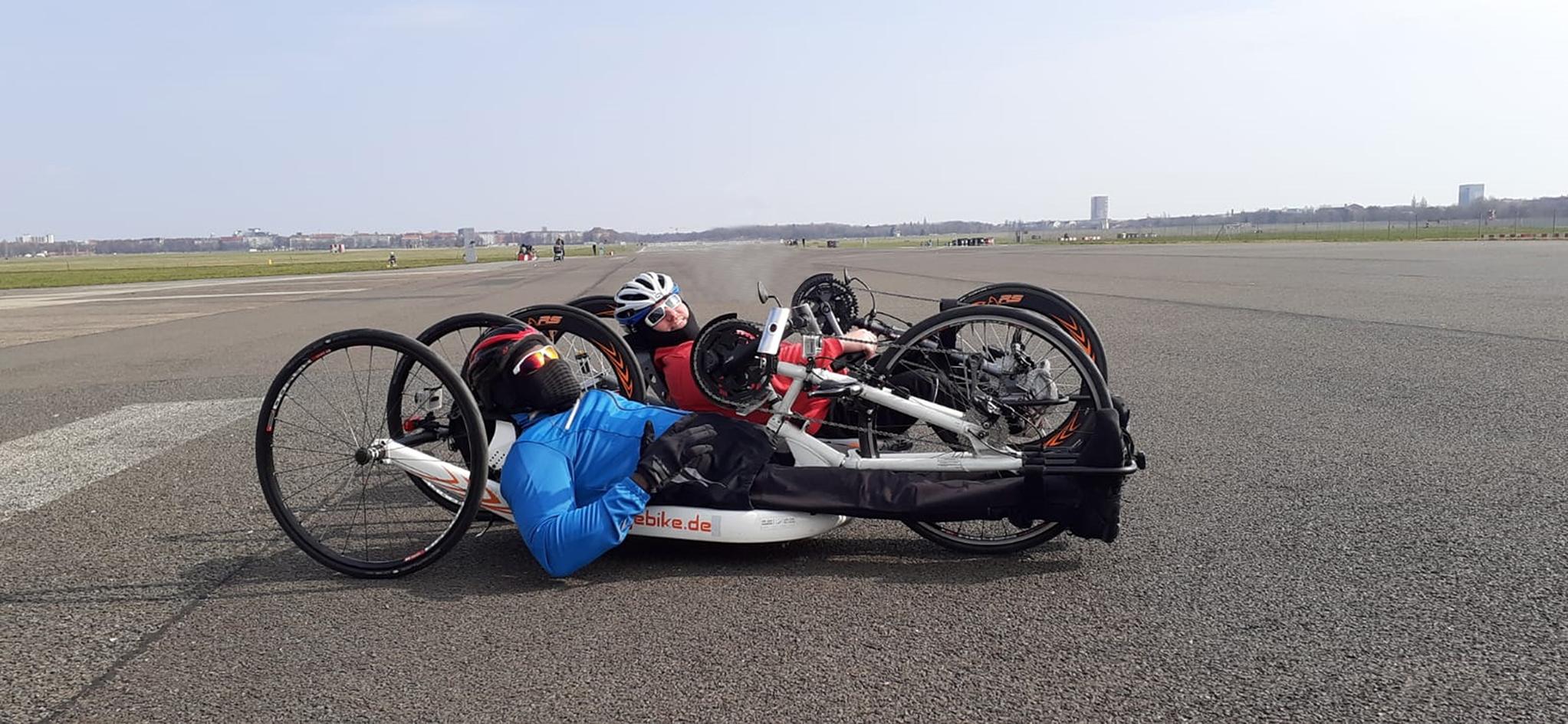 Ein Foto zeigt Christoph Pisarz in einem Liegebike. Neben ihm ein weiterer Fahrer. Beide haben Helme auf und liegen flach, knapp über dem Boden in einem dreirädrigen aerodynamisch geformten Gefährt. In Höhe der Hände ist eine Handkurbel angebracht, über deren Drehen man sich fortbewegen kann, Foto: André Dounia.
