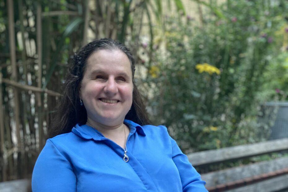 Blind sein – Mandy Hamann sitzt in einer meerblauen Bluse auf einer Bank. Dahinter ragen grüne Pflanzen empor. Hamann lächelt in die Kamera. Mit beiden Händen berührt sie ein aufgeschlagenes Braille-Buch auf ihrem Schoß, Fotorechte: Mandy Hamann.